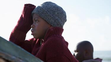 Szenenbild: Ein Junge in Pullover und Mütze im Profil, er blickt in die Ferne