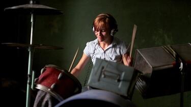 Szenenbild: Eine Frau am selbstzusammengestellten Schlagzeug