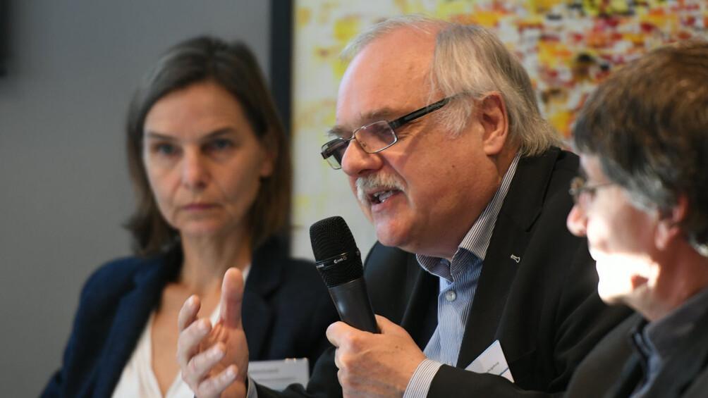 Bild von Podiumsteilnehmer Horst Niesyto mit Mikrofon, im Hintergrund weitere Teilnehmende