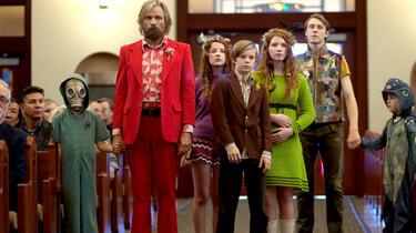 Szenenbild: Ben und seine sechs Kinder in bunter, etwas verrückter Kleidung bei der Trauerfeier in der Kirche