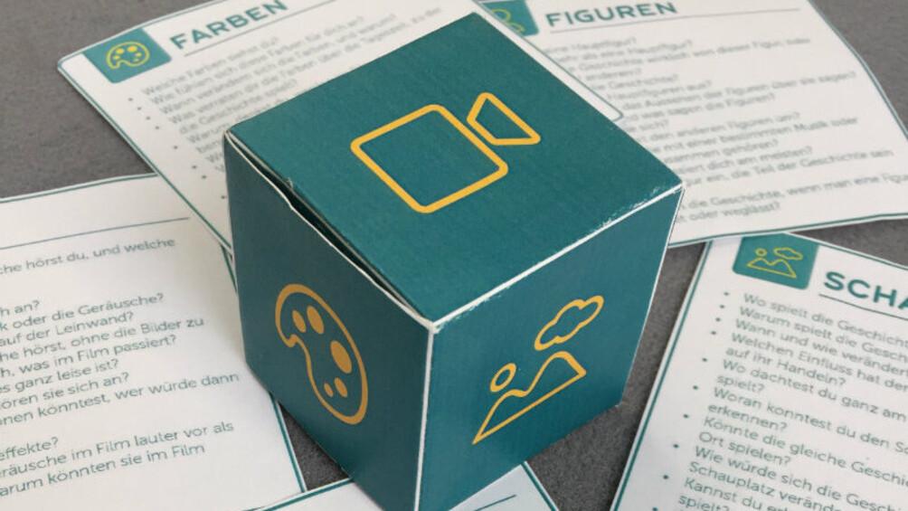 fertig gebastelter Würfel und ausgeschnittene Fragekarten