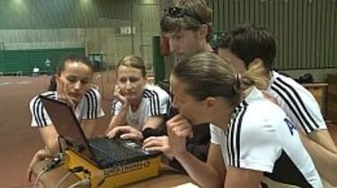 Szenenbild: Die jungen Mädchen sitzten in Trikots vor einem Laptop