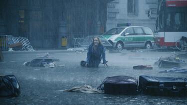 Szenenbild: Hanna auf einer Straße knieend, auf der Koffer und Kleidungsstücke liegen, im Hintergrund verlassene Fahrzeuge, es regnet