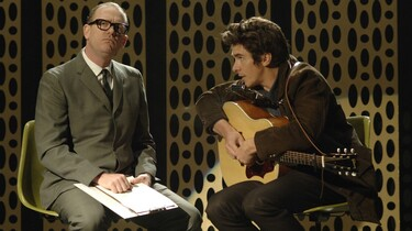 Szenenbild: Zwei Männer sitzen auf Stühlen. Der eine hält eine Gitarre in der Hand