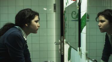 Szenenbild: Charo in der Schultoilette, sie schaut sich im Spiegel an und ist von der Seite zu sehen