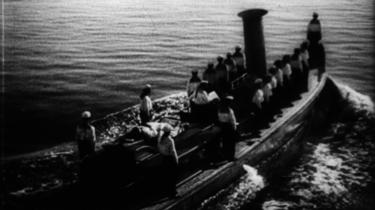 En Schiff mit Matrosen auf hoher See. Schwarz-weiß Bild.