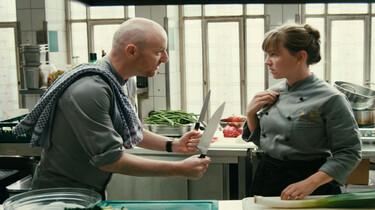 Szenenbild: Zwei Köche in einer Küche, er redet offenbar heftig auf sie ein