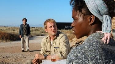 Szenenbild: Zwei Männer und eine Frau auf einer staubigen Landstraße