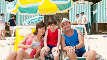 Szenenbild: Der kleine Nick mit seinen Eltern auf einer Urlaubslieger unter einem Sonnenschirm
