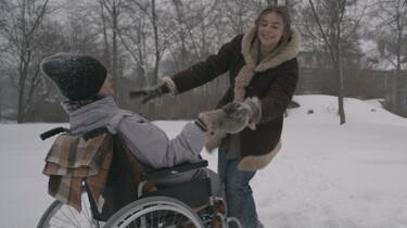 Szenenbild: Mateus, im Rollstuhl sitzend, und eine junge Pflegerin toben im Schnee