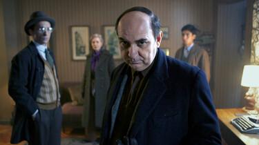 Szenenbild: Pablo Neruda im Vordergrund in einem etwas düsteren Raum, im Hintergrund weitere Personen