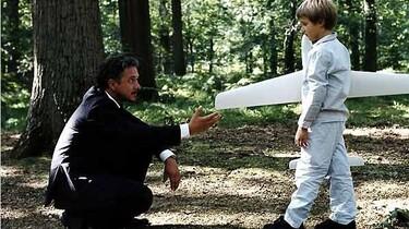 Szenenbild: Der Junge und sein Vater im Wald mit dem Flugzeug