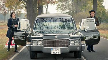 Szenenbild: Der Junge Tom und ein älterer Mann stehen rechts und links von einem Bestattungswagen mit geöffnenten Autotüren