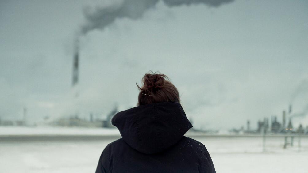 Eine Frau mit Dutt ist von hinten zu sehen. Sie schaut auf eine weite Industrielandschaft.