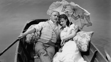 Diederich Heßling mit Sonnenschirm und Frau im Arm in einem Ruderbot.