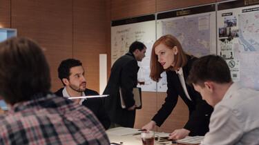 Szenenbild: Miss Sloane in Arbeitssituation mit Kollegen, an einem Tisch stehend