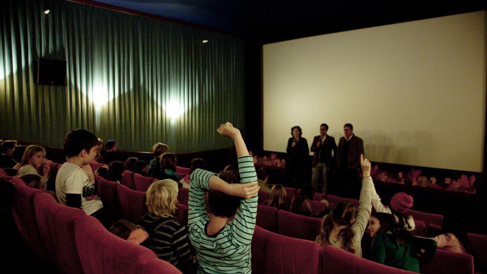 Blick zur Leinwand in einem Kinosaal, im Vordergrund meldet sich ein Kind, das von hinten zu sehen ist.