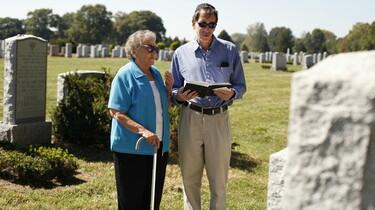 Szenenbild: Eine alte Frau mit Stock steht auf einem Friedhof neben einem Mann, der ein Buch in der Hand hält