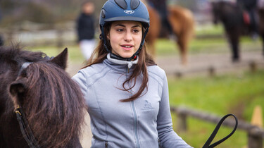 Szenenbild: Mädchen mit Reiterhelm führt ein braunes Pferd, dessen Kopf zu sehen ist