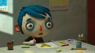 Szenenbild aus dem Puppentrickfilm: Zucchini sitzt an einem Tisch und malt ein Bild. Die Figur hat einen übergroßen Kopf, riesigen Augen und blaue Haare