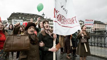 Szenenbild:Demonstrationszug von Frauen mit Transparenten, im Vordergrund Nora
