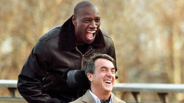 Driss fährt Philippe im Rollstuhl spazieren. Sie lachen herzhaft.