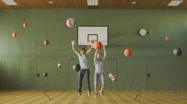 Szenenbild: Zwei Mädchen Hüpfen in einer Turnhalle, um sie herum fliegen lauter Bälle