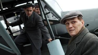 Szenenbild: Zwei Männer steigen aus einem kleinen Flugzeug aus