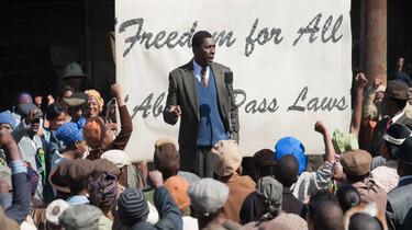 Szenenbild: Der junge Nelson Mandela vor einem Plakat mit der Aufschrift Freedom for All