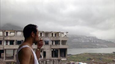 Szenenbild: rauchender Mann vor Häuserruine