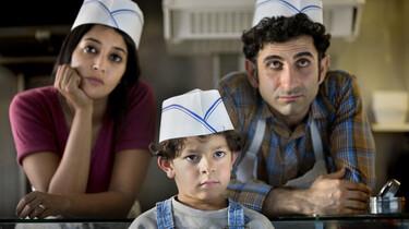 Szenenbild: Mutter, Vater und Sohn mit weißen Papiermützen in einem Imbisswagen auf Kunden wartend