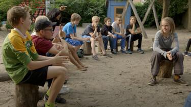 Szenenbild: Eine Gruppe von Kindern und Erwachsenen im Halbkreis auf einem Spielplatz sitzend