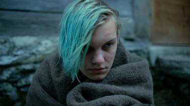 Szenenbild: Matteo, mit blau gefärbten Haaren, sitzt in eine graue Decke gehüllt vor der Hütte