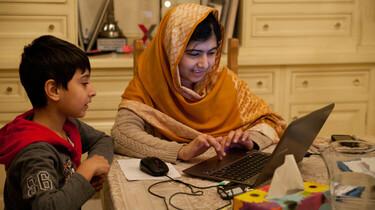 Szenenbild: Malala mit ihrem kleinen Bruder am Küchentisch am Laptop