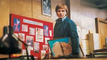 Alex steht mit einem Porträit von Erich Honecker in der Hand vor einem Schaubild zum Thema 40 Jahre DDR.