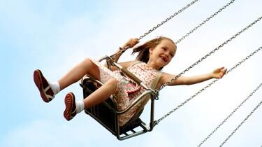 Szenenbild: Ein Mädchen schaukelt im Kettenkarussell