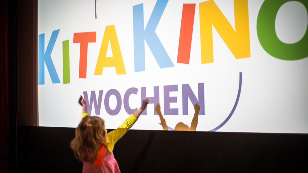 Hüpfendes Kind im Kino vor Logo der KitaKinoWoche auf Leinwand