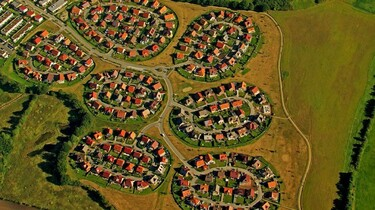 Szenenbild: Luftaufnahme ovaler Siedlungen