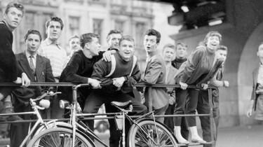 Junge Leute stehen gut gelaunt in eine Richtung schauend an der S-Bahn-Station