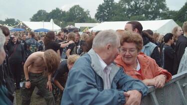 Szenenbild: An der Bühne: ein altes Ehepaar, im Hintergrund Heavy matal Fans
