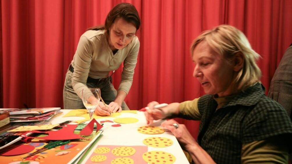 Workshopteilnehmerinnen an einem Tisch mit bunten Papierschnipseln