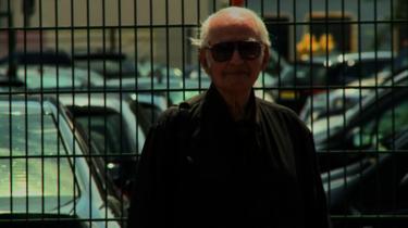 Leon Schwarzbaum mit Sonnenbrille steht vor einem Gitterbaum.