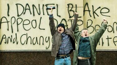 Szenenbild: Daniel Blake und ein Passant reißen die Arme in die Höhe vor der Wand, die Daniel mit einer Parole besprüht hat