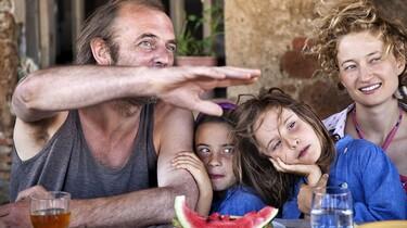 Die Familie sitzt an einem Tisch redet und isst Wassermelone.
