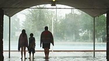 Szenenbild: Die Familie von hinten gesehen, sie schauen auf den im Regen liegenden Swimming-Pool