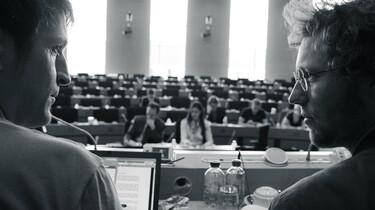 Szenenbild: Jan Philipp Albrecht und ein Kollege schauen vom Bildrand auf den Plenarsaal