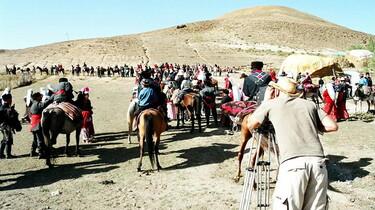 Szenenbild: Ein Mann mit Kamera und viele Menschen vor einem sandigen Hügel