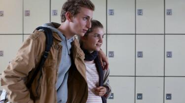 Szenenbild: Maxime und Mélanie Arm in Arm vor einer Wand mit Schließfächern