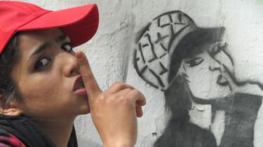 Szenenbild: Soniat mit Basecap und Finger über den Lippen vor einem Graffitti, das sie oder eine sehr ähnliche Person darstellt