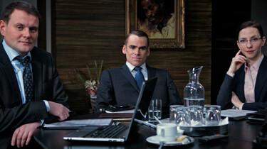 Szenenbild: Die drei Unternehmensberater bei einem Business-Termin am Tisch sitzend